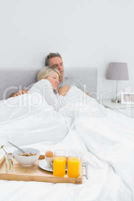 Couple sleeping with breakfast tray at end of bed