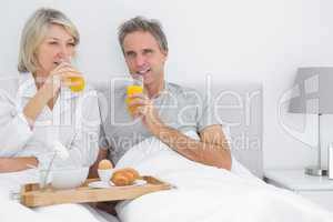 Couple drinking orange juice having breakfast in bed