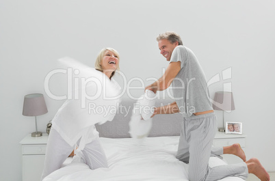 Fun couple having a pillow fight