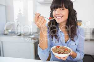 Attractive brunette eating bowl of cereal and fruit