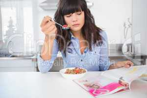 Pretty brunette having cereal and reading magazine
