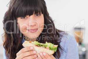Happy brunette having a salad sandwich