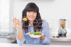 Pretty brunette having a healthy salad for lunch
