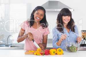 Happy friends preparing a salad together