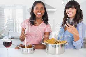 Cheerful friends preparing dinner together