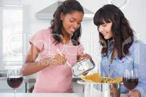 Cheerful friends preparing spaghetti dinner together