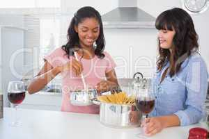 Cheerful friends making spaghetti dinner together