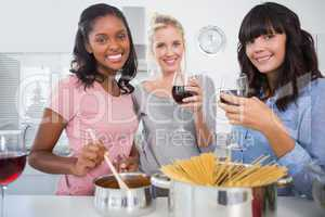 Cheerful friends making spaghetti dinner together and drinking r