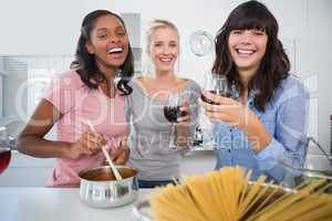 Laughing friends making spaghetti dinner together and drinking r