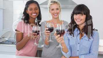Happy friends enjoying glasses of red wine