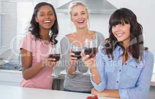 Cheerful friends enjoying glasses of red wine