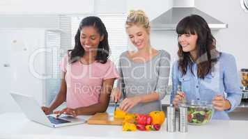 Happy friends making salad and using laptop for recipe