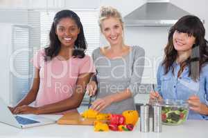 Cheerful friends making salad and using laptop for recipe lookin