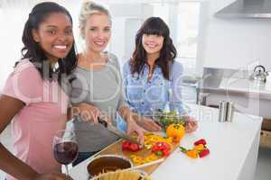 Cheerful friends preparing a meal together looking at camera