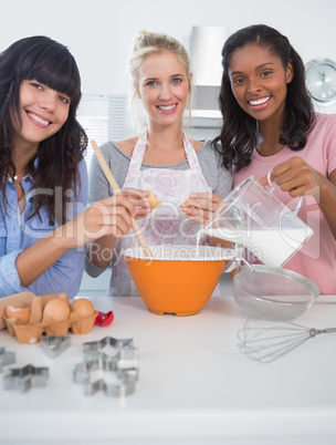Happy friends making pastry together looking at camera