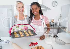 Cheerful woman showing freshly baked cookies with friend