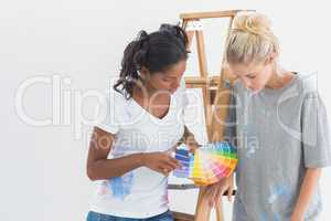 Cheerful housemates choosing colour for wall