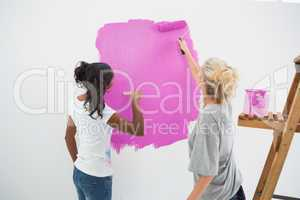 Happy young housemates painting wall pink