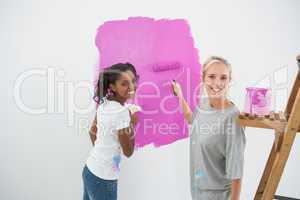 Smiling young housemates painting wall pink