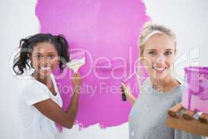 Cheerful young housemates painting wall pink