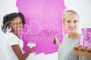 Smiling housemates painting wall pink