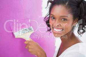 Smiling young woman painting her wall in pink