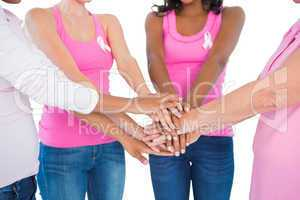 Women wearing breast cancer ribbons putting hands together