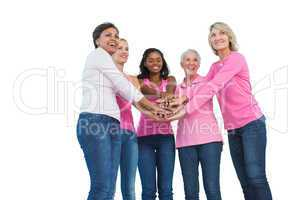 Women wearing breast cancer ribbons with hands together and smil