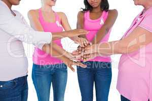 Women wearing breast cancer ribbons with hands together