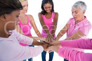 Women wearing pink and ribbons for breast cancer putting hands t