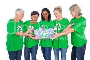 Team of female environmental activists holding box of recyclable