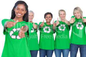 Team of female environmental activists smiling at camera and giv