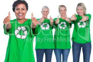 Happy women wearing green recycling tshirts giving thumbs up
