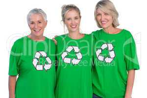 Three women wearing green recycling tshirts smiling at camera