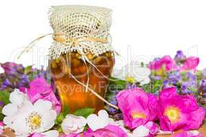 Honey jar with blossoms and herbs