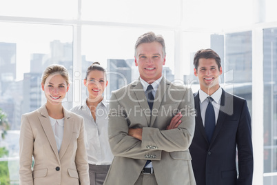 Boss with his arms folded standing with smiling colleagues behin