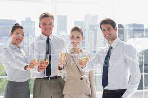 Smiling team of business people honoring a success with champagn