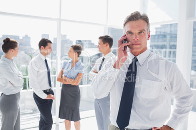 Boss on the phone standing in a modern office