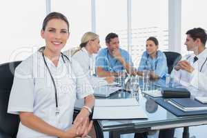 Smiling woman doctor looking at the camera in front of her team