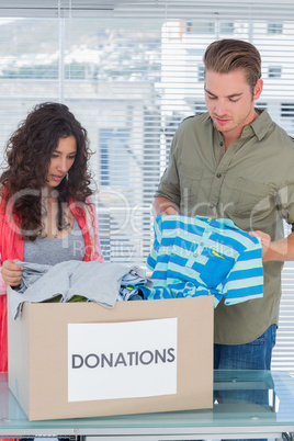 Serious volunteers taking out clothes from a donation box