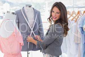 Attractive fashion designer measuring blazer