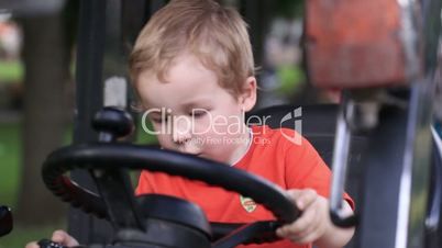 Kid turns the wheel of the tractor