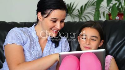 smiling mother and daughter using tablet computer