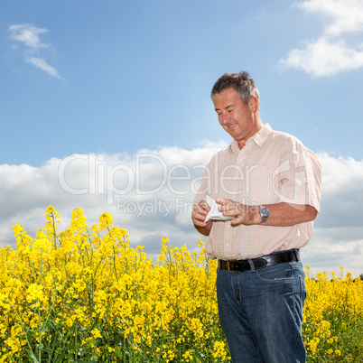 Man with hay fever on blooming rapeseed field