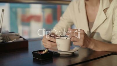 young beautiful woman is drinking coffee in a restaurant eating dessert