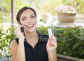 Young Adult Woman Holding Cell Phone and Credit Card Outside