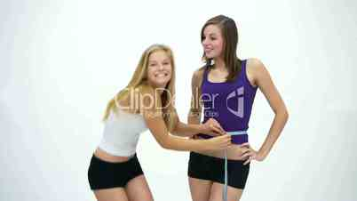 D1080 Two slim young girls measuring belly and are happy. Version 1