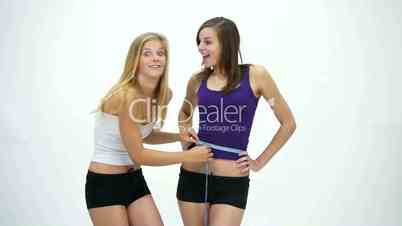D1080 Two slim young girls measuring belly and are happy. Version 2
