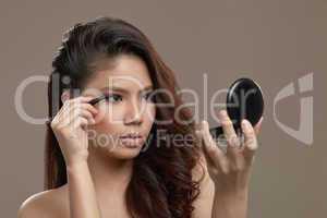 female asian applying eye liner