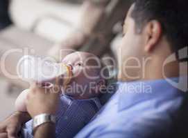 Happy Hispanic Father Bottle Feeding His Mixed Race Son